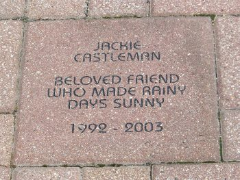 Example memorial brick. Reads Jackie Castleman, beloved friend who made rainy days sunny. 1992 - 2003