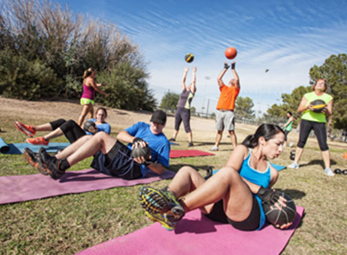 Group training outside with weighted exercise balls