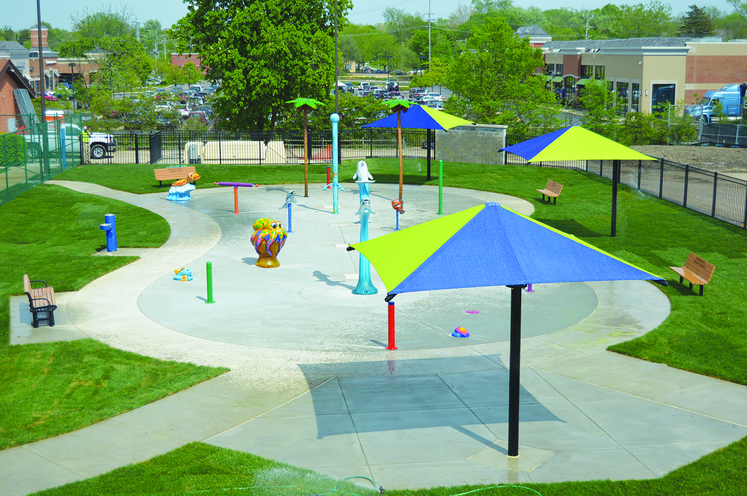 Splashpad aerial view. Features include multiple sprinklers and water spouts, mounted waterguns, seating, and shaded areas.
