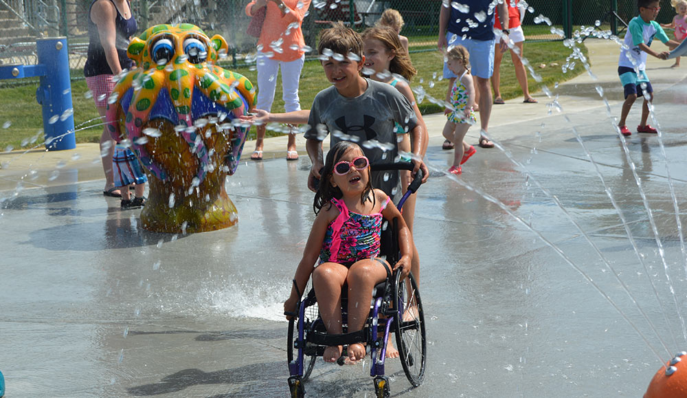 Splashpad young children's spray park. A young child in a wheelchair is being assisted by another child, enjoying the park.