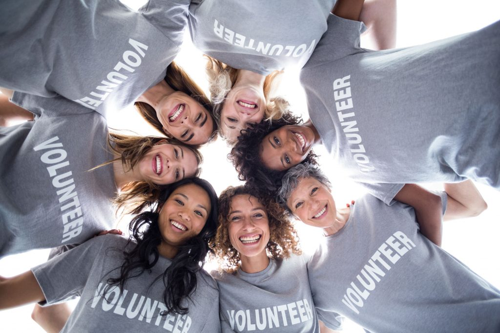 Adult women standing in a circle holding hands, looking down at the camera, wearing shirts that say volunteer